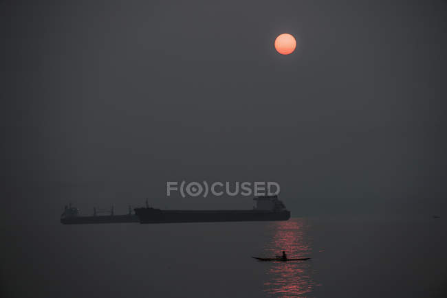 Silhouette freight boats on sea against sky at night — Stock Photo