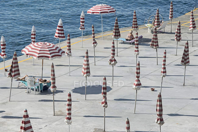 High angle view of striped parasols and women on beach — Stock Photo