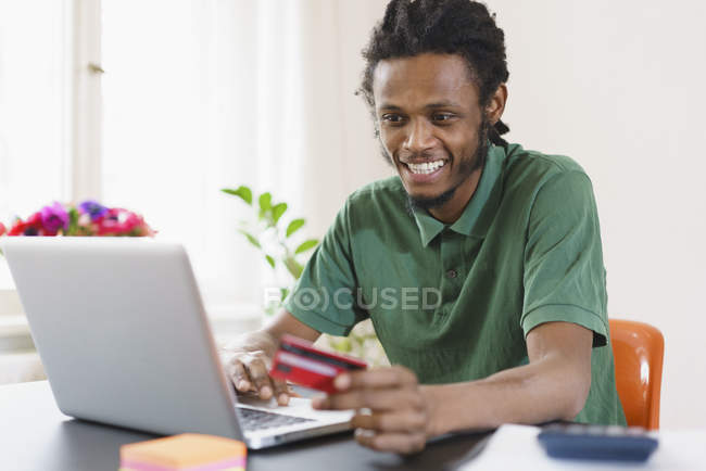 Happy man shopping online through laptop at home — Stock Photo