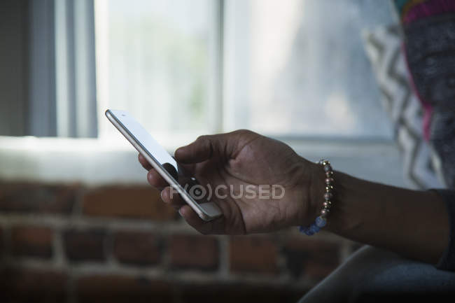 Cropped image of male hand holding mobile phone at home — Stock Photo