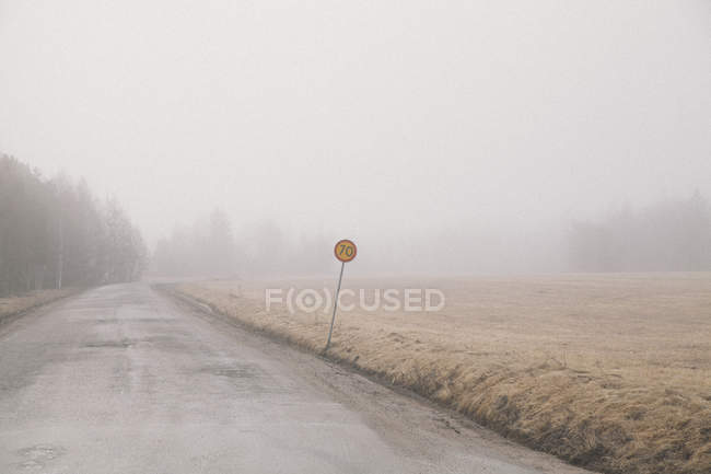 Tilted road sign by countryside field in foggy weather — Stock Photo