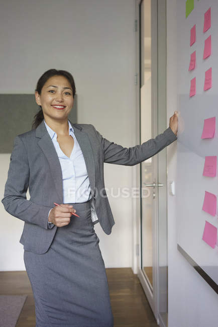 Портрет бизнесвумен, стоя на клей примечания над доски в творческих офис — стоковое фото