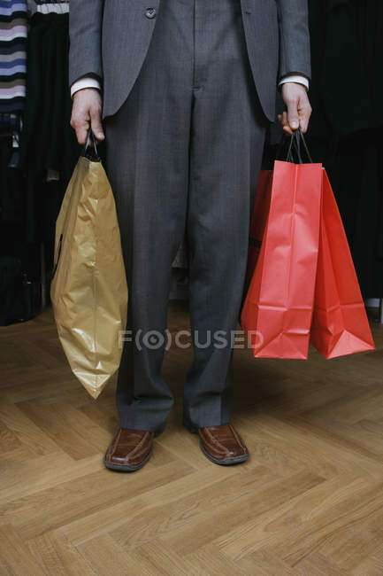 Low section of man in formal attire holding three shopping bags — Stock Photo