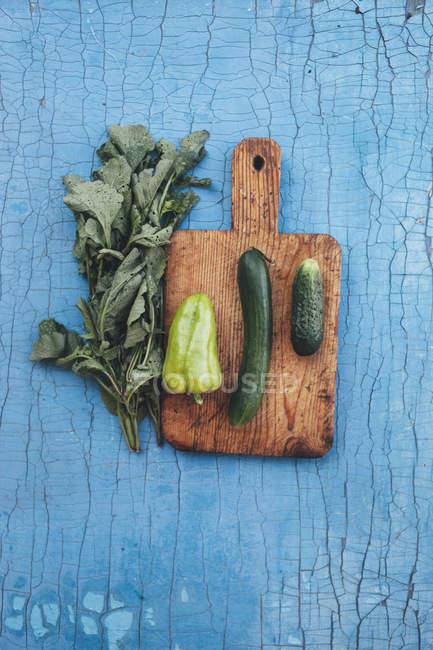 Вид сверху зеленые овощи на разделочной доске на деревянный стол — стоковое фото