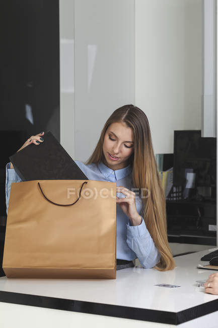 Saleswoman putting box in shopping bag at shoe store — Stock Photo