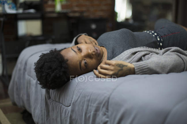 Young woman lying on bed at home — Stock Photo
