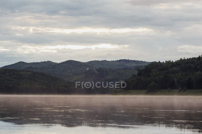 Scenic view of river and mountains against cloudy sky — Stock Photo