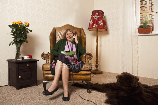 Senior woman on phone sitting in armchair at home — Stock Photo