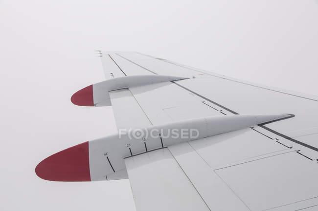 Кадроване зображення крила літака в туманний білий небо — стокове фото