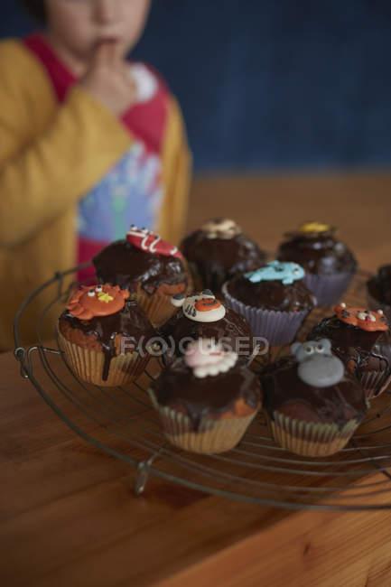 Cupcakes de cultivo en refrigeración rack en mesa con chica en fondo - foto de stock