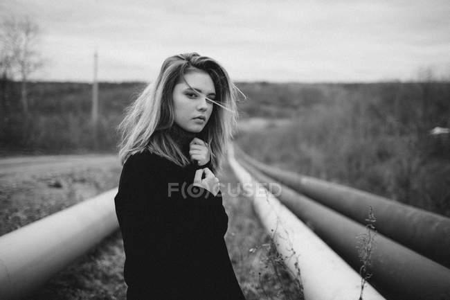 Портрет девочки-подростка, стоящей посреди труб на поле — стоковое фото