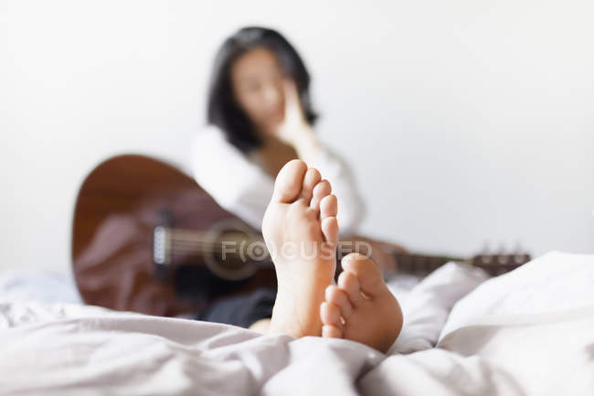 Woman with bare feet holding guitar while resting on bed at home — Stock Photo