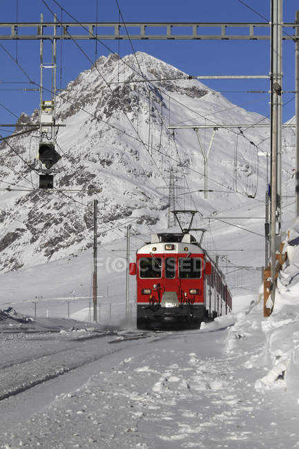 Front view of of red tram in against snowy mountain — Stock Photo
