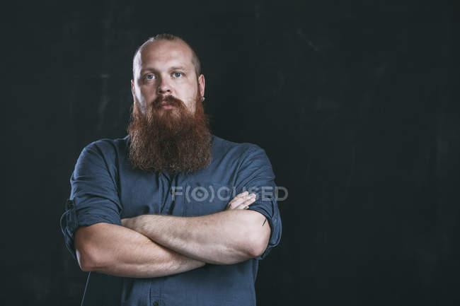 Porträt von Hipster stehen mit verschränkten vor schwarzem Hintergrund — Stockfoto