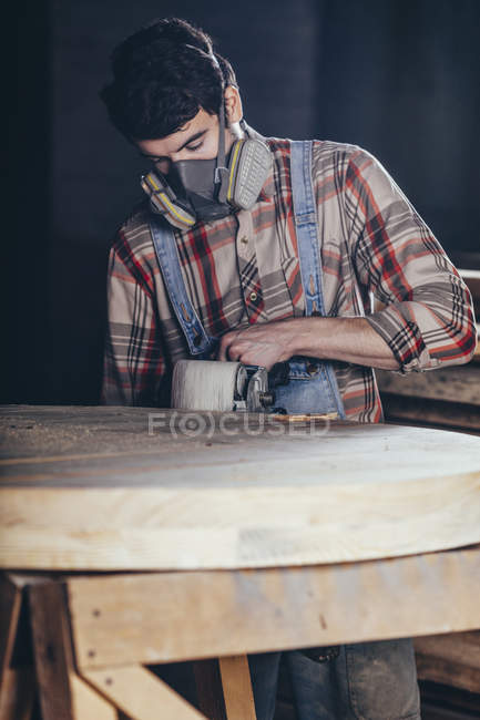 Man using electric sander on wood at workshop — Stock Photo