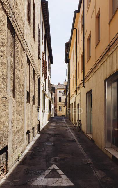 Callejón estrecho en medio de edificios residenciales en la ciudad, Faenza, Italia - foto de stock