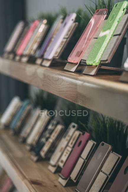 Various phone covers displayed on shelves at store — Stock Photo