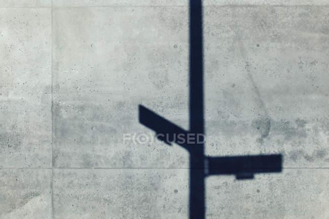 Schatten des Hinweisschildes an grauer Betonwand — Stockfoto