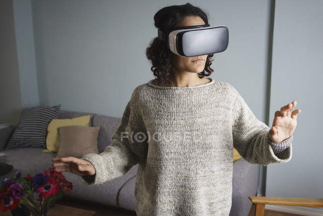 Woman using virtual reality headset while standing in living room — Stock Photo