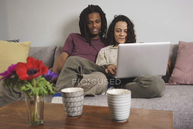 Young multi-ethnic couple using laptop while sitting on sofa at home — Stock Photo