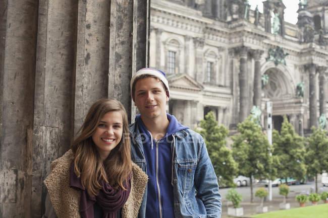 Ritratto di giovani amici sorridenti in piedi accanto alla colonna dell'Altes Museum contro la Cattedrale di Berlino — Foto stock