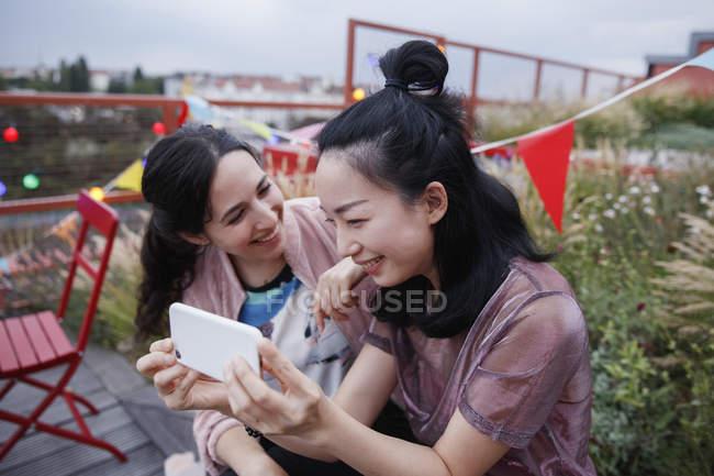 Glückliche Frau schaut Freundin an, während sie ihr Smartphone auf der Terrasse benutzt — Stockfoto