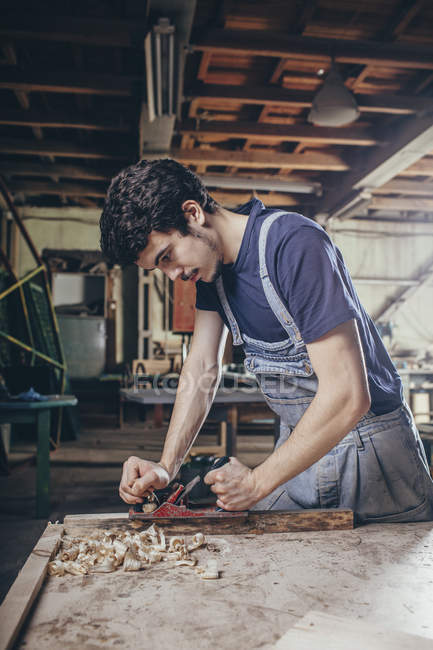 Young carpenter planing timber at workshop — Stock Photo
