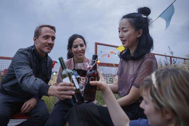 Multi-étnica amigos brindando garrafas de vinho durante a festa no pátio — Fotografia de Stock