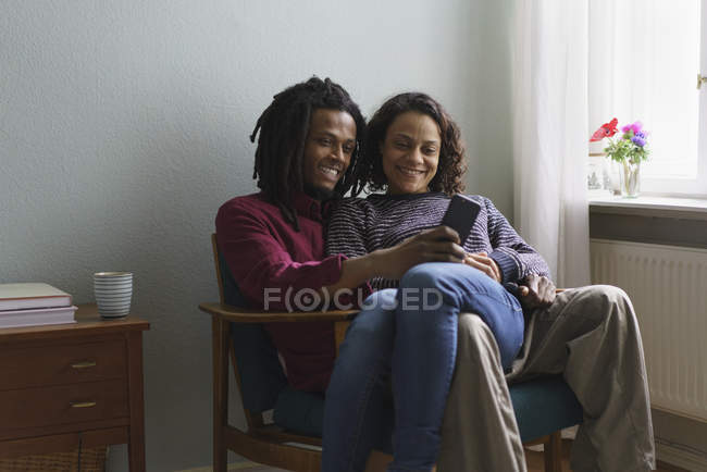 Smiling multi-ethnic couple using smart phone while sitting on armchair at home — Stock Photo