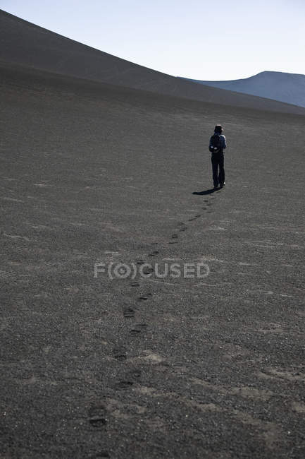 Rear view of woman walking over arid terrain — Stock Photo