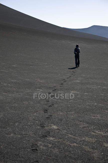 Задній вид жінка ходьба по посушливій місцевості — стокове фото