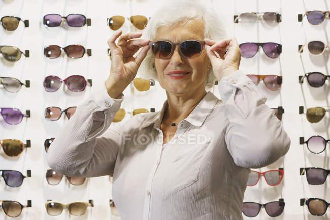 Femme âgée souriante portant des lunettes de soleil tout en étant debout au magasin — Photo de stock