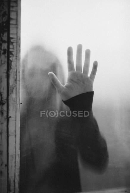 Teenager berührt Glas mit Handfläche — Stockfoto