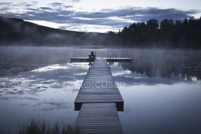 View to pier on calm lake in foggy weather — Stock Photo