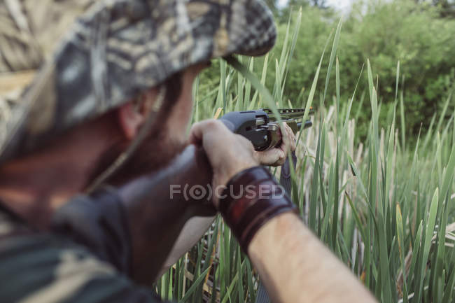 Over shoulder view of hunter aiming rifle on field — Stock Photo