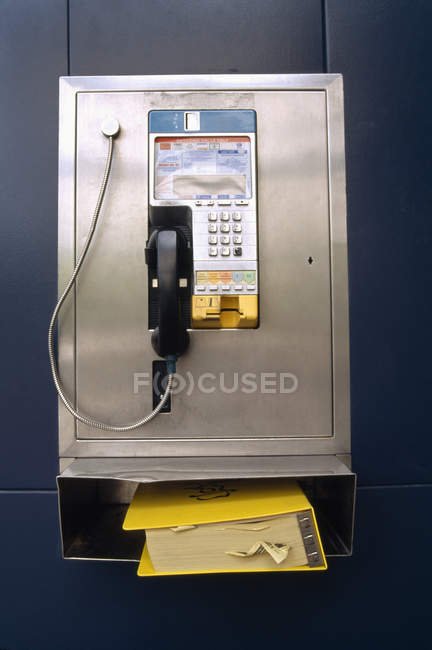 Front view of public payphone with telephone book — Stock Photo