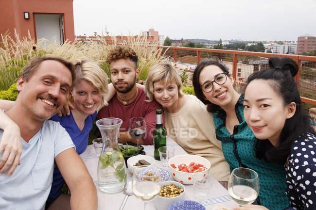 Portrait d'amis heureux assis à la table extérieure au patio — Photo de stock