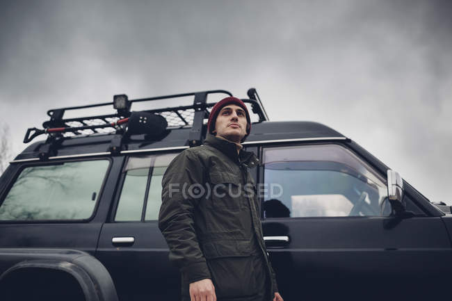 Man standing next to sports utility vehicle against cloudy sky — Stock Photo
