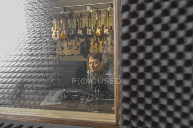 Musician using computer seen from window glass at recording studio — Stock Photo