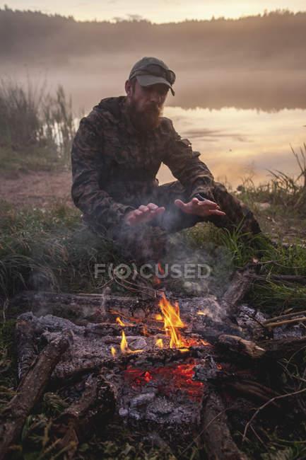 Hunter réchauffant mains sur le feu de joie tout en étant assis sur le terrain au bord du lac pendant le coucher du soleil — Photo de stock