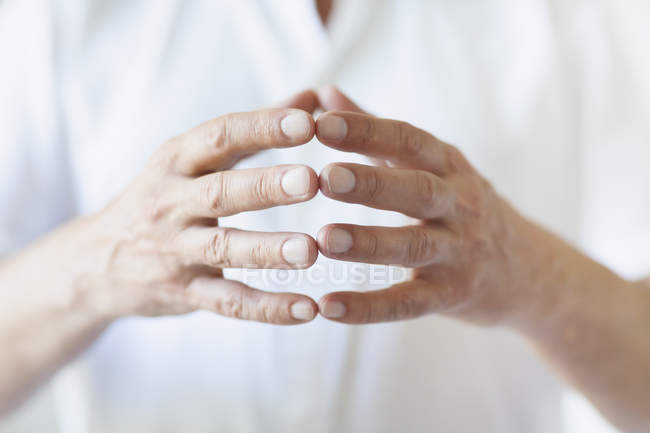 Midsection of man wearing white t-shirt touching fingers — Stock Photo