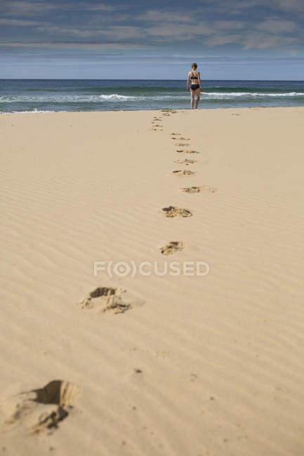 Крупным планом зрения следы на пляже, ведущих к женщине — стоковое фото