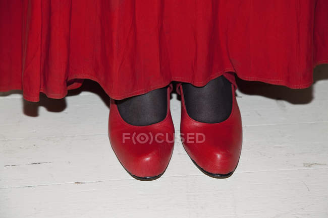 Crop woman wearing red skirt and red shoes — Stock Photo