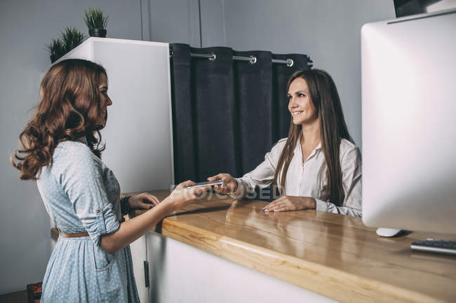 Young saleswoman handing repaired mobile phone to female customer at counter — Stock Photo