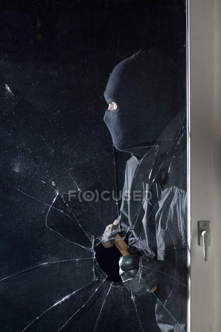 Criminal breaking into window with hammer at night — Stock Photo