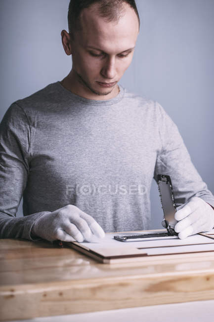 Young male technician repairing mobile phone at electronics store — Stock Photo
