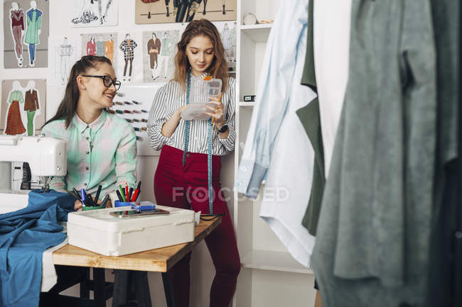 Happy designer looking at female trainee holding container in design studio — Stock Photo