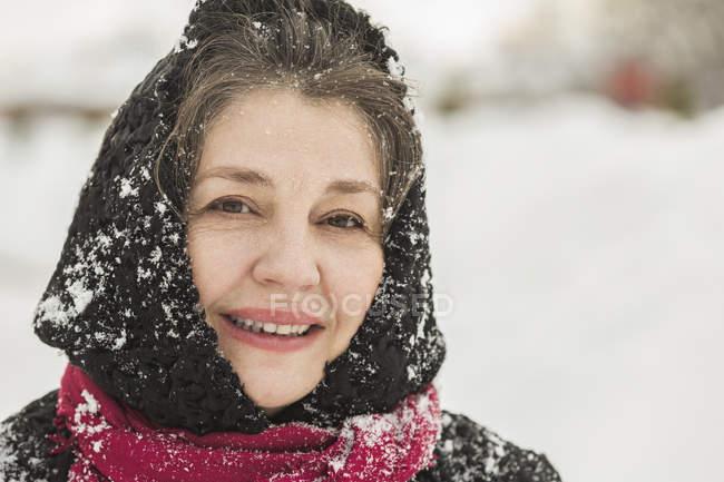 Porträt einer lächelnden Seniorin in schneebedeckter Winterkleidung — Stockfoto