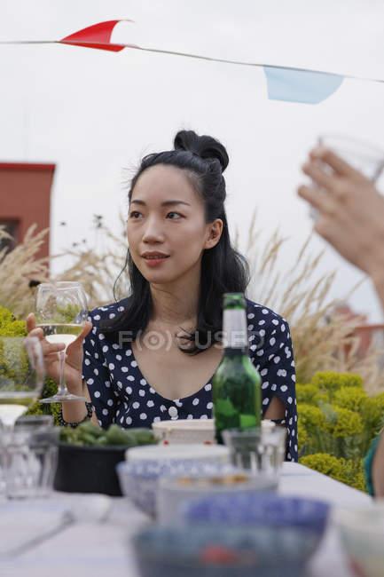 Nachdenkliche Frau hält Weinglas, während sie während der Party am Tisch sitzt — Stockfoto