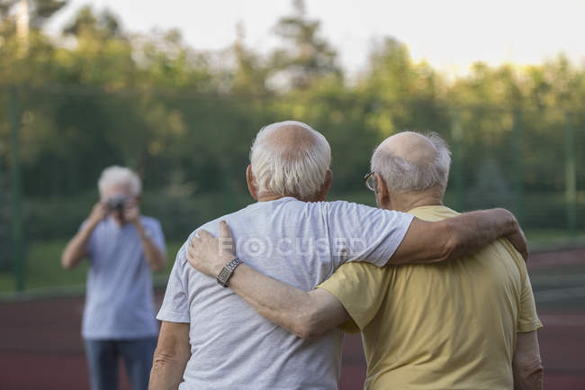 Rear view of senior friends standing with arm around while photographing — Stock Photo